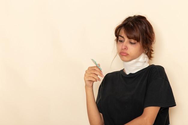 Giovane femmina malata di vista frontale con alta temperatura e sensazione di malessere che tiene le pillole sulla superficie bianca Foto Gratuite