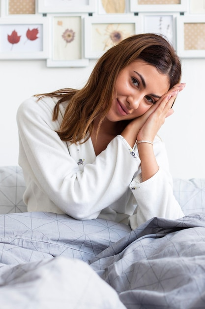 Front view of sleepy woman in bed wearing pajamas Free Photo