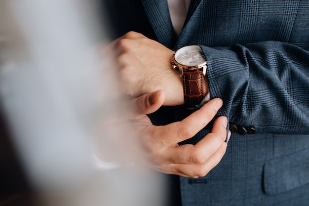 Front view of a sleeve of man's suit and hands with stylish watch Free Photo