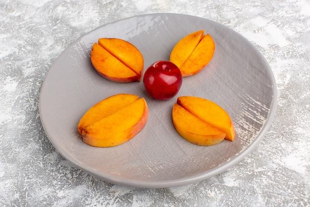 Вид спереди нарезанные свежие персики внутри тарелки, выложенной на светло-белом столе. Бесплатные Фотографии