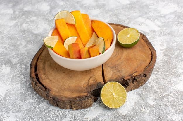 正面図は、明るい白の背景にレモンとプレート内の新鮮な桃をスライスしました。 無料写真