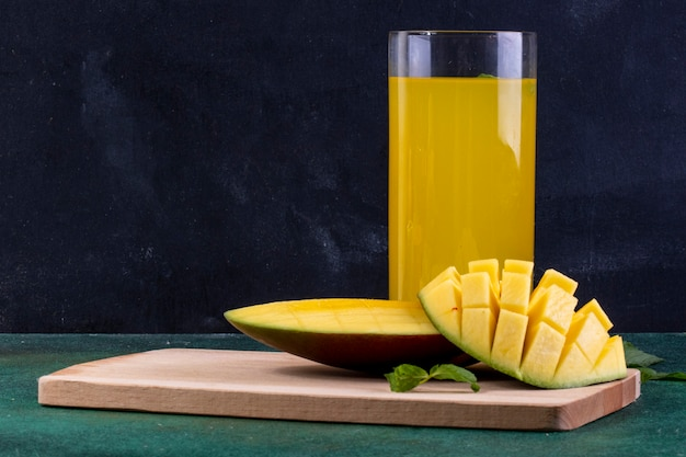 Front view sliced mango on blackboard with a glass of orange juice and mint leaves Free Photo