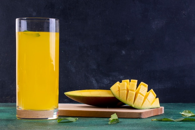 Front view sliced mango on a blackboard with a glass of orange juice Free Photo