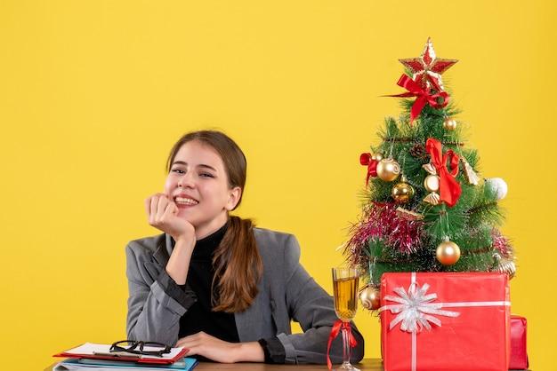 Vista frontale ha sorriso la ragazza che si siede allo scrittorio che mette la mano al suo cocktail dei regali e dell'albero di natale della mascella Foto Gratuite