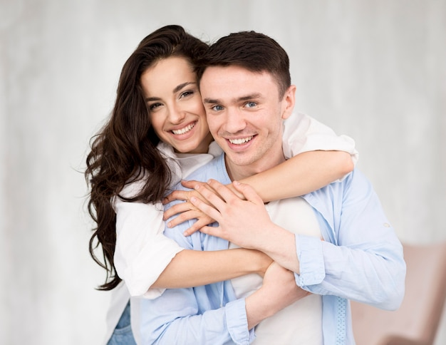 Front view of smiley couple posing embraced Free Photo