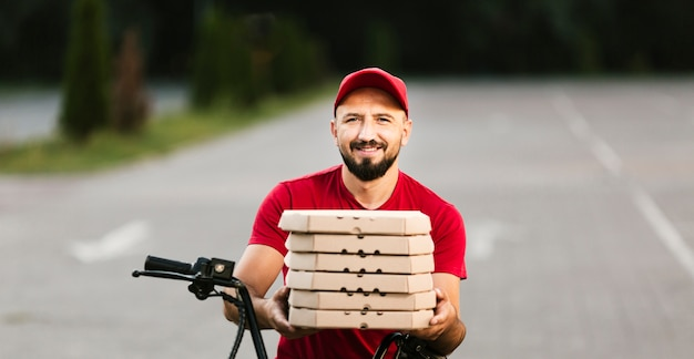 Front view smiley delivery guy holding pizza boxes Free Photo