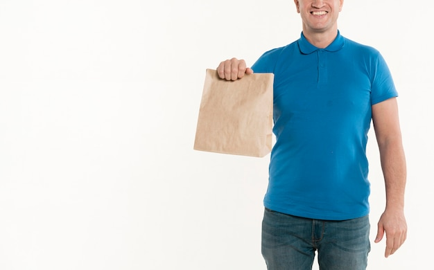 Front view of smiley delivery man holding paper bag Free Photo