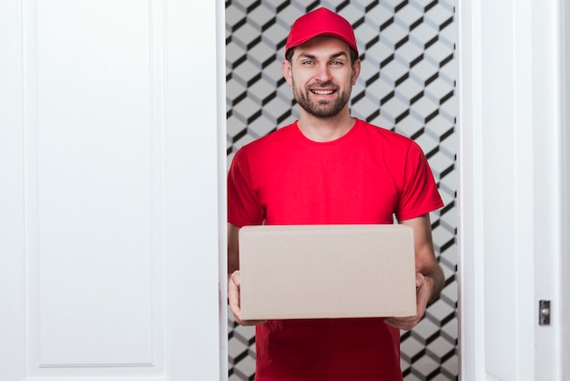 Front view smiley delivery man wearing red uniform Free Photo