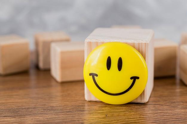 Vista frontale della faccina sorridente sul blocco di legno Foto Gratuite