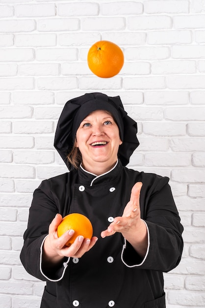 Front view of smiley female chef joggling with oranges Free Photo