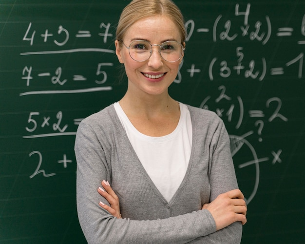 Front view of smiley female teacher posing in front of blackboard Free Photo