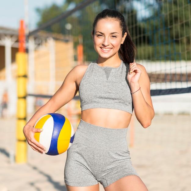 Vista frontale del giocatore di pallavolo femminile di smiley sulla spiaggia che posa con la palla Foto Gratuite