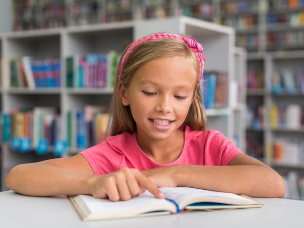 Смайлик вид спереди делает свою домашнюю работу в библиотеке Бесплатные Фотографии