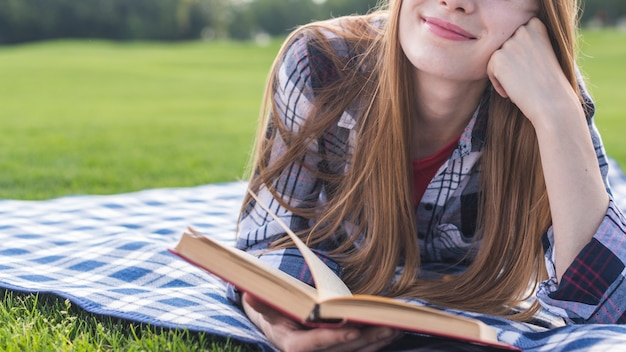 Front view smiley girl reading a book Free Photo