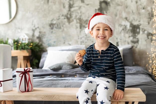 Ragazzo di smiley vista frontale che tiene un biscotto Foto Gratuite