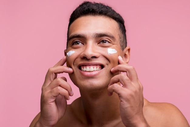 Vista frontale dell'uomo sorridente che applica la crema sul suo fronte Foto Gratuite