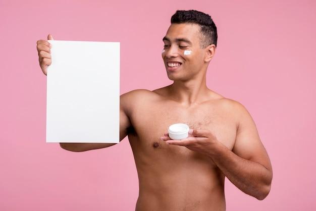 Vista frontale dell'uomo di smiley che tiene la crema per il viso e il cartello in bianco Foto Gratuite