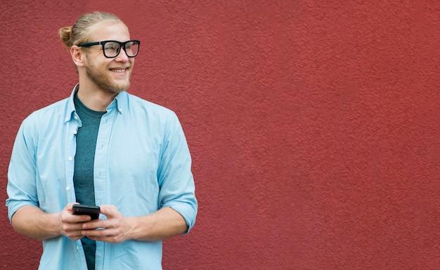 Vista frontale dello smartphone della tenuta dell'uomo di smiley Foto Gratuite