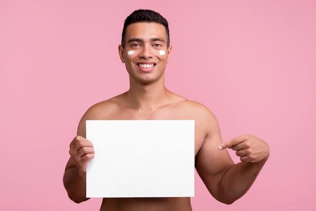 Vista frontale dell'uomo di smiley con crema sul viso che punta al cartello in bianco Foto Gratuite