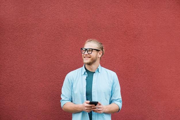 Vista frontale dell'uomo di smiley con lo smartphone Foto Gratuite