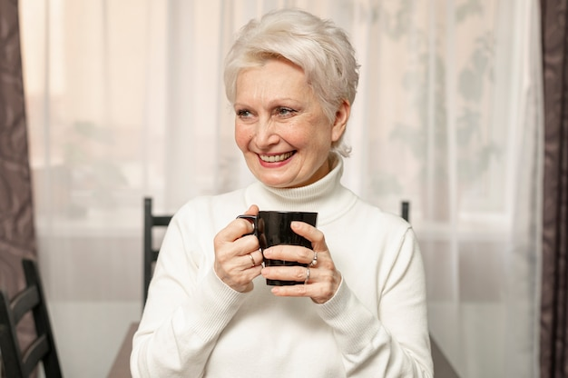 Front view smiley senior female holding cup of coffee Free Photo