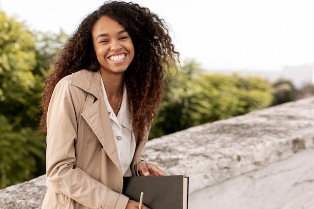 Front view smiley woman holding a book with copy space Free Photo