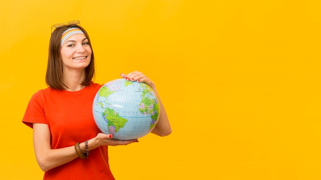 Front view of smiley woman holding globe with copy space Free Photo