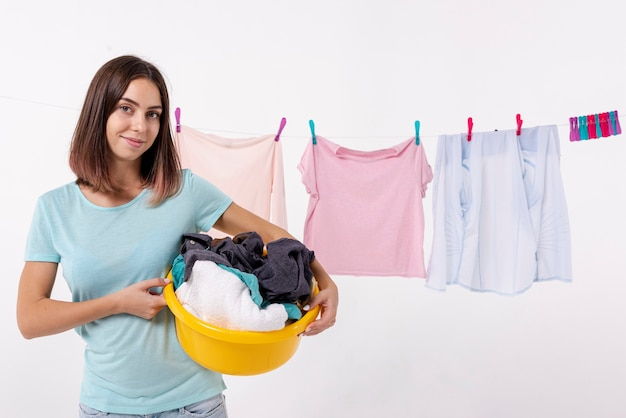 Front view smiley woman holding a laundry basket Free Photo