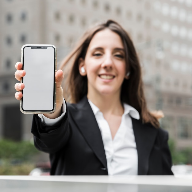 Front view smiley woman holding up her phone Free Photo