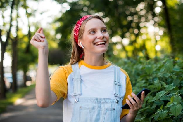 Vista frontale della donna di smiley all'aperto con lo smartphone Foto Gratuite