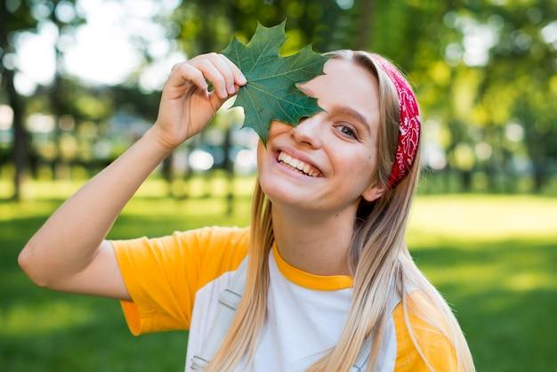 Vista frontale della donna di smiley che propone con il foglio Foto Gratuite