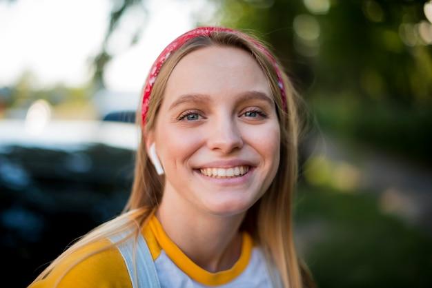 Vista frontale della donna di smiley con auricolari Foto Gratuite