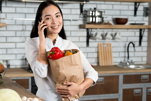 Front view of smiling asian woman talking on mobile phone while holding grocery bag Free Photo