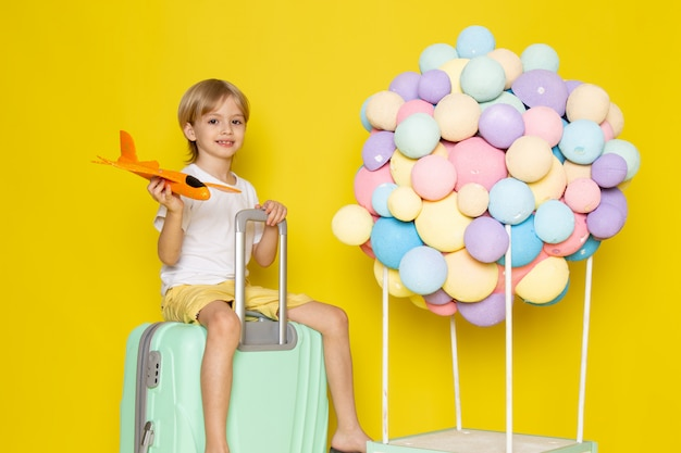 Front view smiling blonde boy playing with orange toy plane along with colorful air balloons on yellow desk Free Photo
