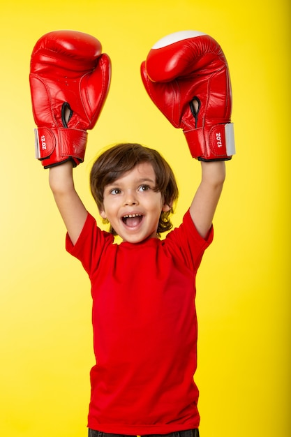 A front view smiling boy in red boxing gloves and without any help Free Photo