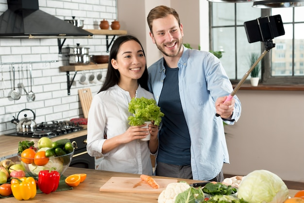Front view of smiling couple taking selfie on mobile phone in kitchen Free Photo