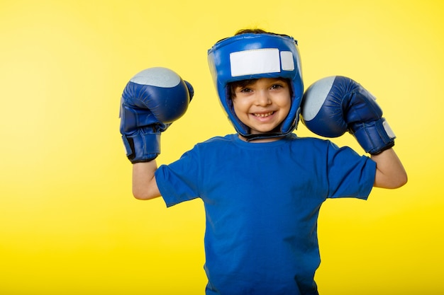 A front view smiling cute boy in blue boxing gloves blue boxing helmet and in blue t-shirt on the yellow wall Free Photo