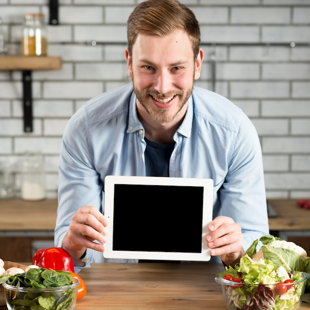 Front view of smiling man showing blank screen digital tablet on kitchen counter Free Photo