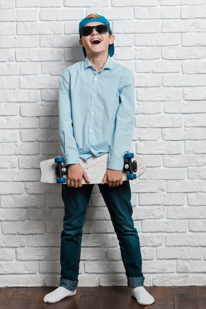 Front view of smiling modern boy with skateboard Free Photo