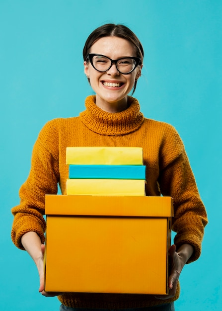 Front view of smiling woman carrying boxes Free Photo