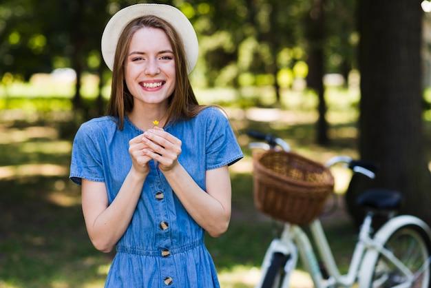 Front view smiling woman holding a flower Free Photo
