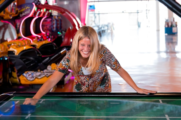 Front view smilling woman playing air hockey Free Photo