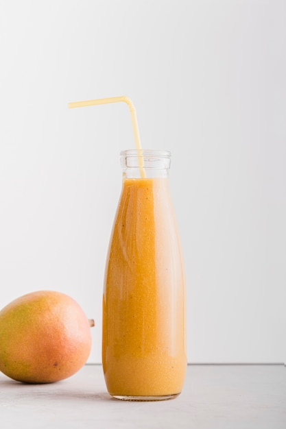 Front view smoothie bottle with straw and mango Free Photo