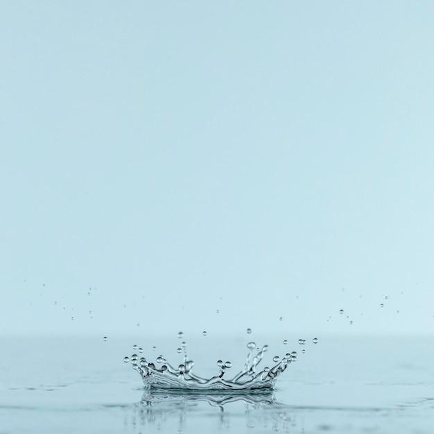 Vista frontale della spruzzata in acqua dalla goccia con lo spazio della copia Foto Gratuite