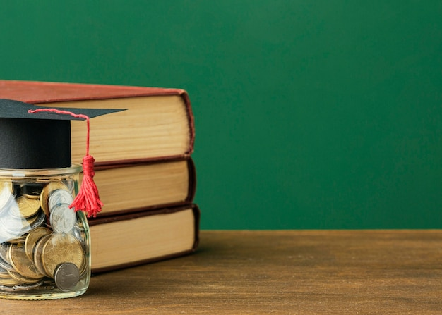 Vista frontale della pila di libri con copia spazio e barattolo di monete Foto Gratuite