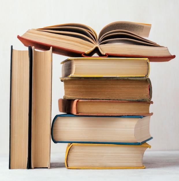 Vista frontale della pila di libri con uno aperto Foto Gratuite