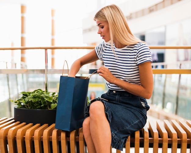 Donna alla moda di vista frontale che controlla i sacchetti della spesa Foto Gratuite