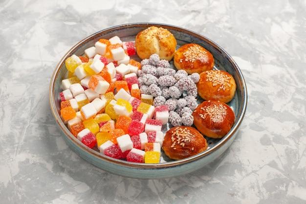 밝은 흰색 표면에 작은 빵이있는 전면보기 설탕 사탕 달콤한 과자 비스킷 설탕 파이 쿠키 무료 사진