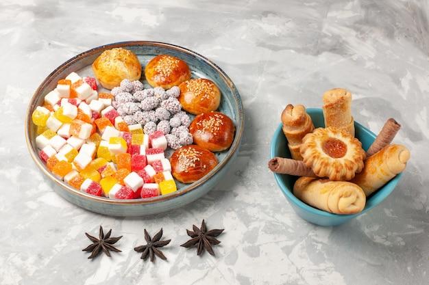 밝은 흰색 표면에 약간의 달콤한 빵과 베이글이있는 전면보기 설탕 사탕 달콤한 과자 비스킷 설탕 파이 쿠키 무료 사진