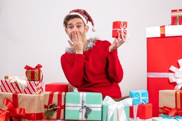 전면보기는 크리스마스 선물 주위에 앉아 젊은 남자를 놀라게 무료 사진